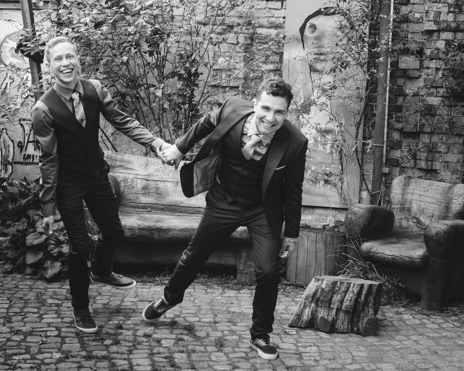 Groom & Groom jumping. Black and white image of gay couple smiling and laughing. Reviews wedding photographer Ireland. Wedding in Berlin, courtyard and graffiti background.